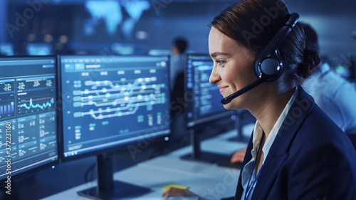 Beautiful Female Data Scientist Works on Personal Computer Wearing a Headset in Big Infrastructure Control and Monitoring Room Fototapet