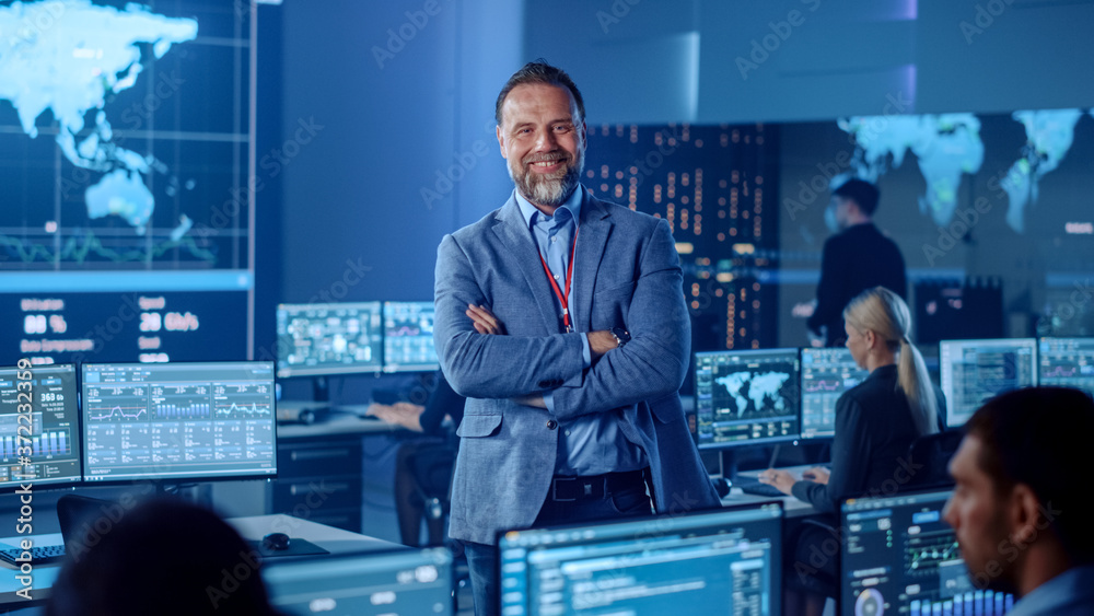 Fototapeta Confident Successful Senior Male Project Leader in a Computer Science Engineer Office Standing with Crossed Arms. He Looks at Camera and Smiles. Control Monitoring Room with a Global Map on Big Screen