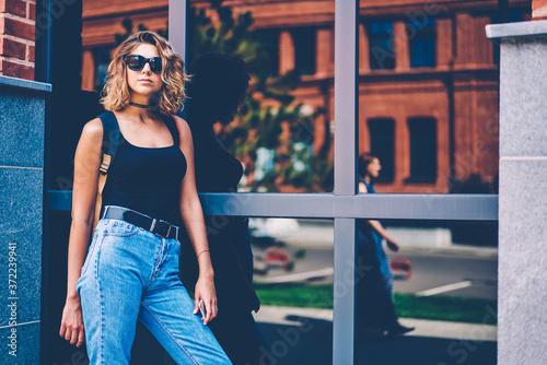 Obraz na plátne Pretty female hipster in stylish eyewear posing near modern architecture buildin