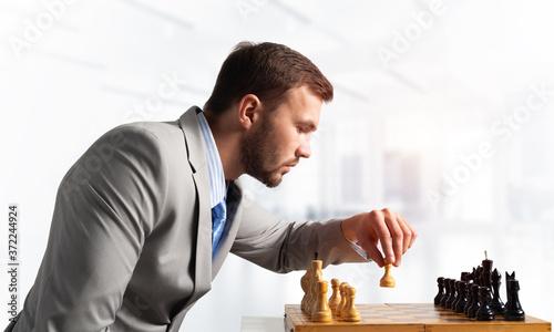 Fototapeta Businessman moving chess figure in chessboard