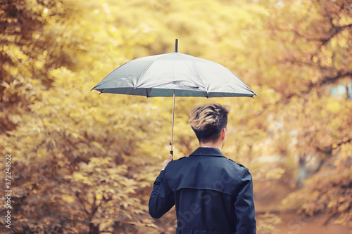 Autumn rainy weather and a young man with an umbrella Fototapete