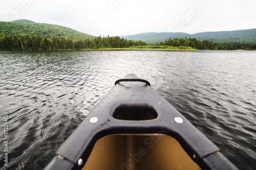 Obraz canoe on a lake in summer on a cloudy summer day - fototapety do salonu