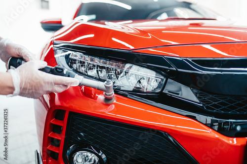 Fotografie, Obraz Car detailing - Worker with orbital polisher in auto repair shop