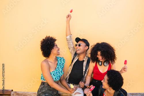 Fototapeta Multi-ethnic group of friends enjoying summertime while eating ice cream. obraz