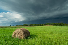 Storm Cloud Over Green Meadow With Hay Bales