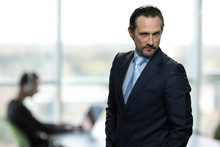 Portrait Of Displeased Strict Businessman. Menacing Businessman On Blurred Office Background.