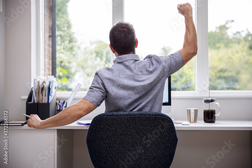 Rear View Of Man Working From Home On Computer  In Home Office Stretching At Des Wallpaper Mural