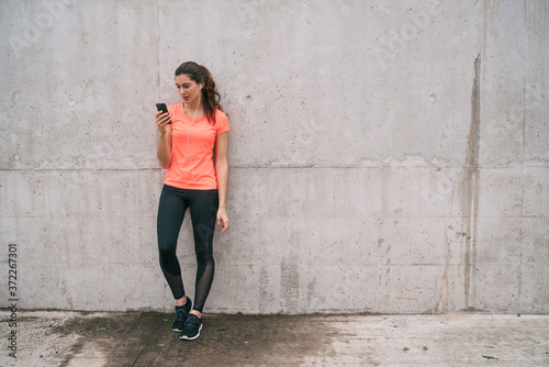 Athletic woman using her phone. Fototapete