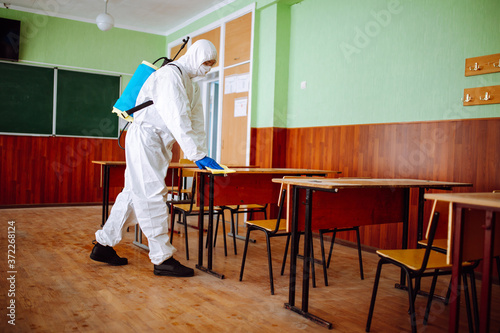 Cuadros en Lienzo A man from disinfection group cleans up the desk at school with a yellow rag