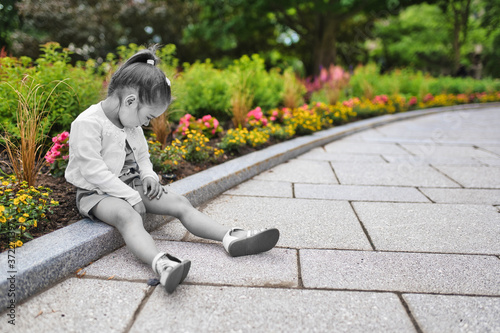 Fotografiet Sad young girl sitting on ground outdoor on summer summer day