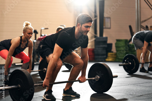 Fit young man lifting weights during a gym class Fototapet