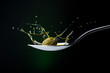 closeup of green olive with splashing oil on a spoon on a dark background