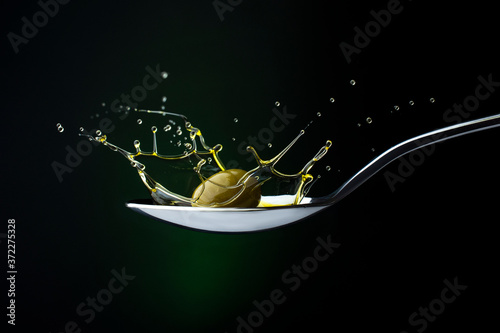 closeup of green olive with splashing oil on a spoon on a dark background Fotobehang