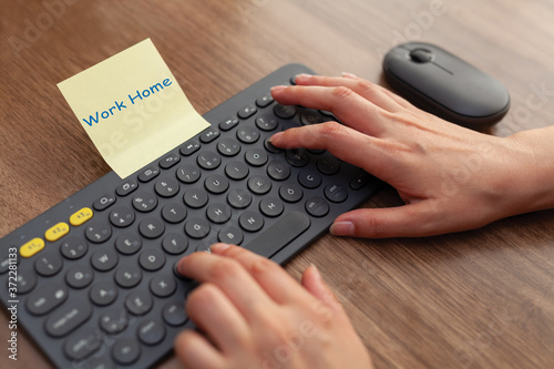 Photo Woman hand touching keys on wireless keyboard and mouse on table