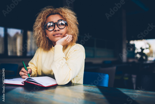 Fotografía Thoughtful young woman in eyeglasses writing to do list of goals writing in diar