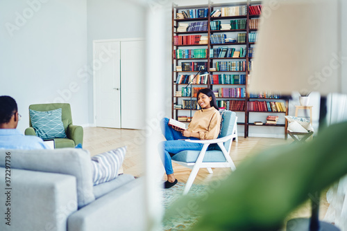 Smiling african american woman sitting in chair in living rood spending free time on hobby while her boyfriend rest on couch, young dark skinned hipsters recreating on leisure in cozy hostel Fototapeta