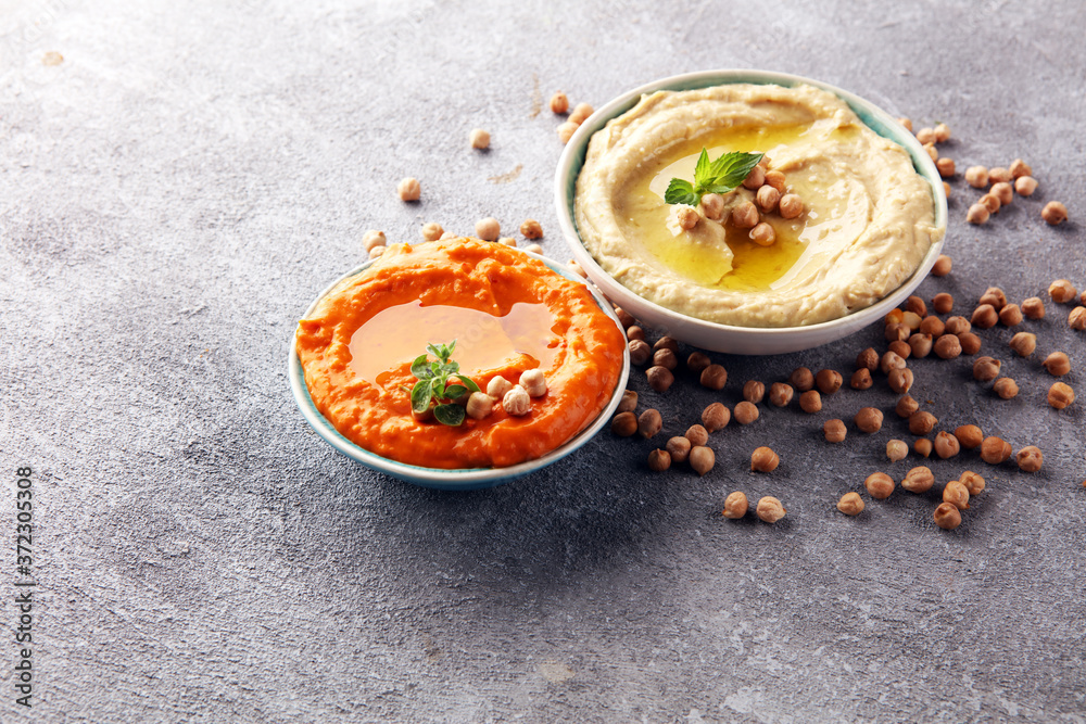 Fototapeta Different hummus bowls. Chickpea hummus, paprika hummus and lentils hummus on rustic table