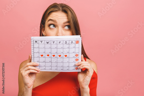 Cuadros en Lienzo Portrait of a funny young girl hiding behind a periods calendar isolated over pink background