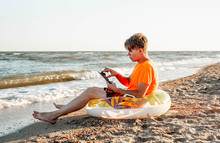 Man Holding A Tablet Sitting On An Inflatable Ring On A Squeak By The Sea