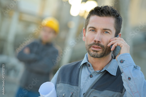 worker using smart phone with factory in the background Fototapet