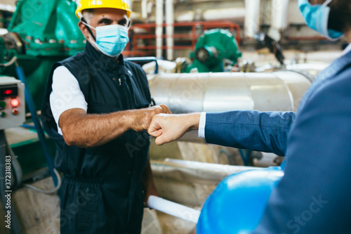 Cuadros en Lienzo businessman and worker handshake indoor industry plant, covid protected with fac