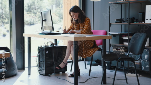 Beautiful happy 30s brunette European freelancer business woman working at modern coworking office table slow motion Wallpaper Mural