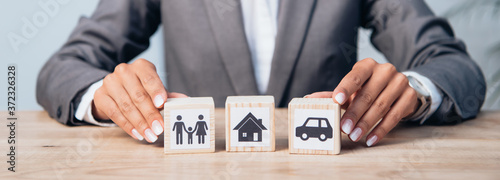 Foto horizontal crop of woman touching wooden cubes with family, car and house