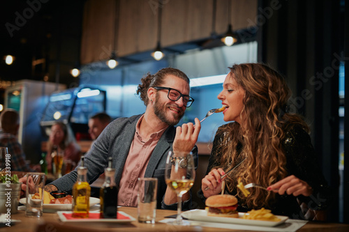 Friends sitting in restaurant and having dinner. Fototapeta
