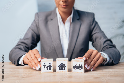 cropped view of woman touching wooden cubes with family, car and house Slika na platnu