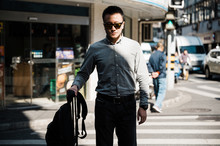 Businesspeople Walking In Pedestrian Crossing And Using Smart Phone