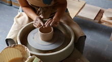 Faceless Master Crafting Pot With Clay On Throwing Wheel