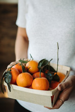 Holding A Basket Of Tangerines