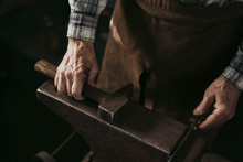 Mature Man Working In Blacksmith Shop.