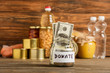 canvas print picture - selective focus of jar with money and donated food on wooden background, charity concept