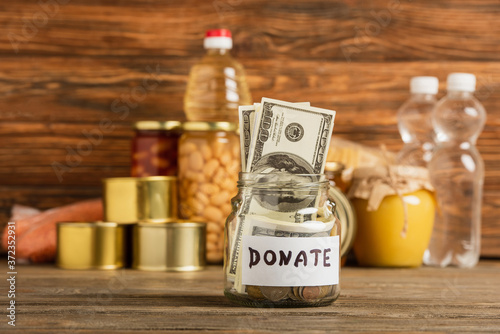 Fotografija selective focus of jar with money and donated food on wooden background, charity