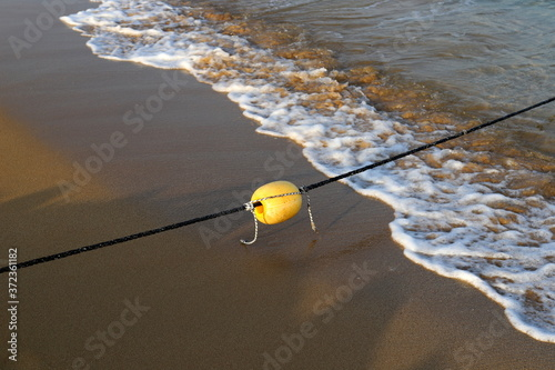 Fotografie, Obraz a rope with buoys to fence off a safe swimming place on a sandy beach on the sho