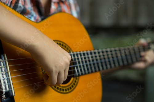 Fotografia, Obraz Acoustic guitar, the hands of a young musician play the guitar.