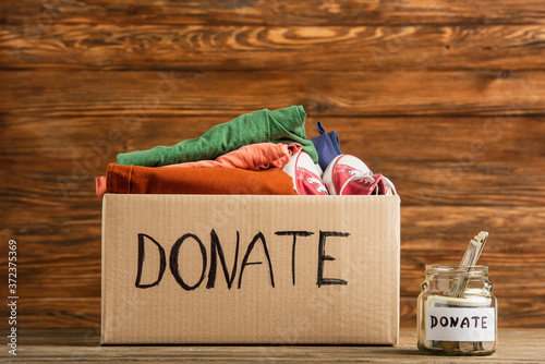 money in jar near cardboard box with donate lettering and clothes on wooden back Wallpaper Mural