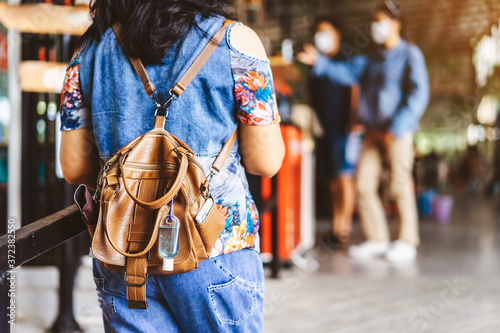 Photo Mini portable alcohol gel bottle to kill Corona Virus(Covid-19) hang on a leather shoulder bag of a woman wear a protective mask at a cafeteria