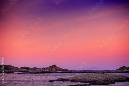 Fjord at sunset. Rocky seashore in the evening. Beautiful nature of Norway. Picturesque Scandinavian landscape. Lofoten islands, Norway