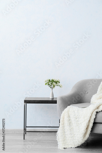 Soft armchair and table near light wall in room Wallpaper Mural
