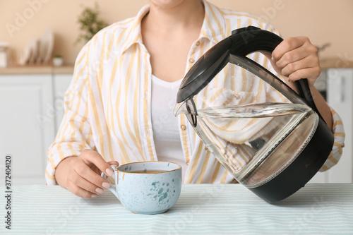 Fotografiet Woman making tea in kitchen