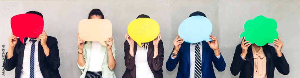 Fototapeta Group of business people holding a empty copyspace speech bubble icon while standing against grey background