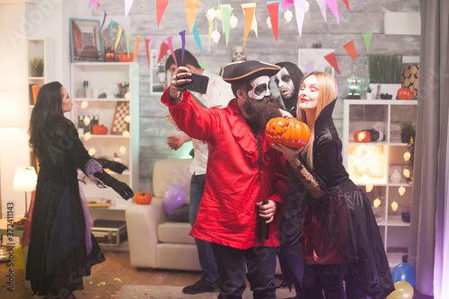 Fotografía Bearded medieval pirate taking a selfie with beautiful vampire woman at halloween party