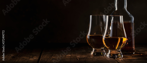 Fotografering Scotch Whiskey without ice in glasses and bottle, rustic wood background, copy s