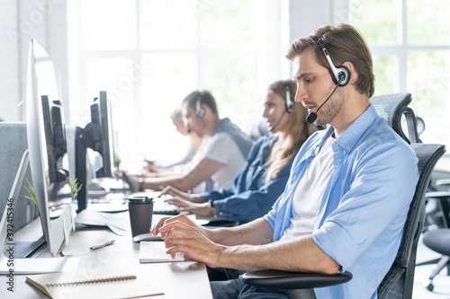Tela Young handsome male customer support phone operator with headset working in call center