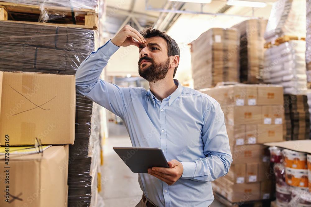 Fototapeta Nervous young attractive bearded businessman leaning on box in warehouse, holding tablet and thinking about problem while holding his head.