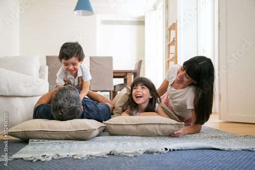 Joyful funny parents and little kids laughing and having fun, romping on living room carpet, enjoying time at home Fototapete