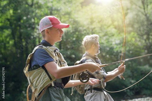 Obraz na plátně A father and his son fly fishing in summer on a beautiful trout river with clear