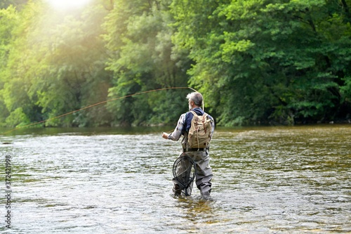 Obraz na plátně Man fly fishing in the summer in a beautiful river with clear water